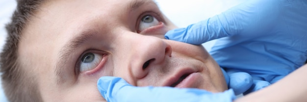 Lekarz w rękawiczkach badający błonę śluzową pacjentów ocena wzroku pacjentów