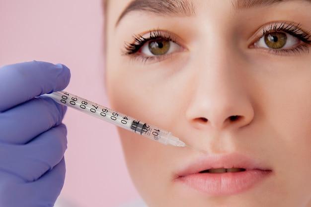 Lekarz w rękawiczkach daje kobiecie zastrzyki z botoksu w usta
