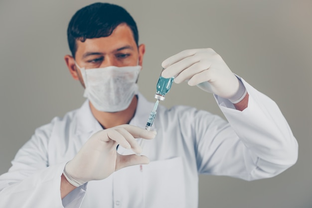 Lekarz w rękawiczkach i masce napełnia strzykawkę do fiolki. widok z boku poziomy
