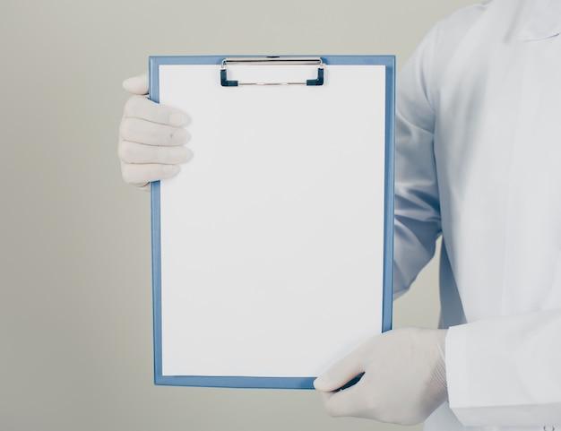 Lekarz w rękawiczkach patrząc i trzymając uchwyt na papier pionowo. widok z boku.