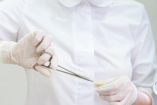 Lekarz w rękawiczkach za pomocą chirurgicznego forcepsto pomocy opaski otwartej
