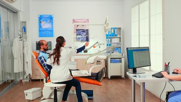 Lekarz w sali konsultacyjnej bada pacjenta z śliniakiem stomatologicznym przed interwencją stomatologiczną siedząc na fotelu stomatologicznym, podczas gdy pielęgniarka stomatolog umawia się na pisanie na komputerze.