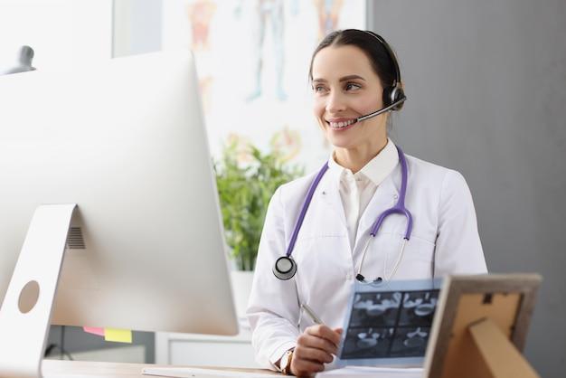 Lekarz w słuchawkach z mikrofonem trzymającym promieniowanie rentgenowskie przed pilotem online ekranu komputera