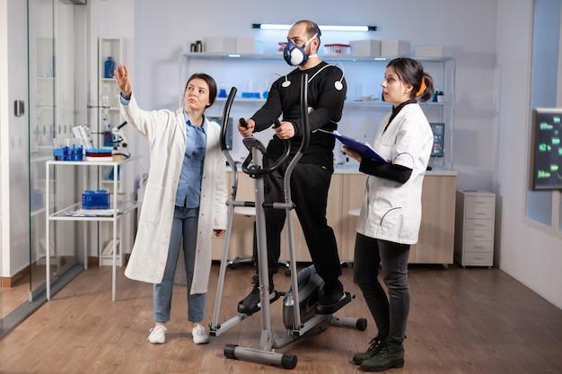 Lekarz w sporcie i sportowiec patrzący na ekran ar z elektrodami przymocowanymi do ciała podczas treningu krzyżowego, sport vo2, tętno ekg cardio. siłownia do ćwiczeń fitness.