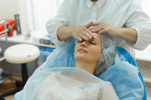 Lekarz w średnim wieku robi masaż twarzy swojej młodej klientce dziewczyny leżącej na kanapie