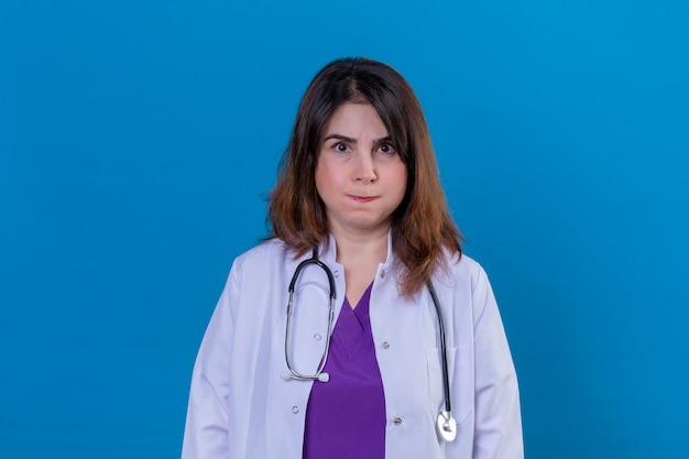 Lekarz w średnim wieku, ubrany w biały fartuch i niezadowolony ze stetoskopu, dmuchający w policzki na niebieskiej ścianie