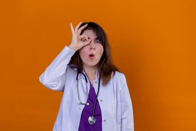 Lekarz w średnim wieku, ubrany w biały fartuch i ze stetoskopem, dobrze się bawiąc ok znak palcami patrząc przez ten znak na odizolowanej pomarańczowej ścianie