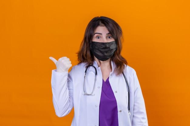 Lekarz w średnim wieku ubrany w biały płaszcz w czarnej ochronnej masce na twarz i ze stetoskopem patrząc na kamerę zaskoczony, wskazując na bok z kciukiem do góry, stojąc nad izolowanym pomarańczowym bac