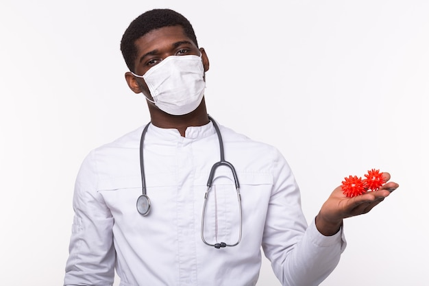 Lekarz w sterylnych rękawiczkach trzymający makietę wirusa covid-19 jako groźny szczep grypy jako pandemia