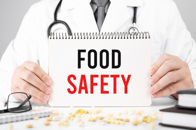 Lekarz w szlafroku trzyma notatnik z tekstem bezpieczeństwo żywności, pojęcie medyczne