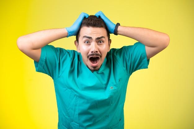Lekarz w zielonym mundurze i masce dłoni obejmującej głowę i krzyczącej.