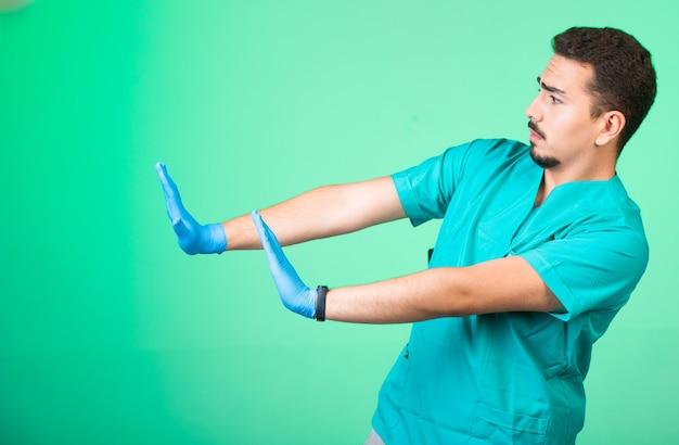 Lekarz w zielonym mundurze i maskach na ręce, oddalający się od niebezpieczeństwa.