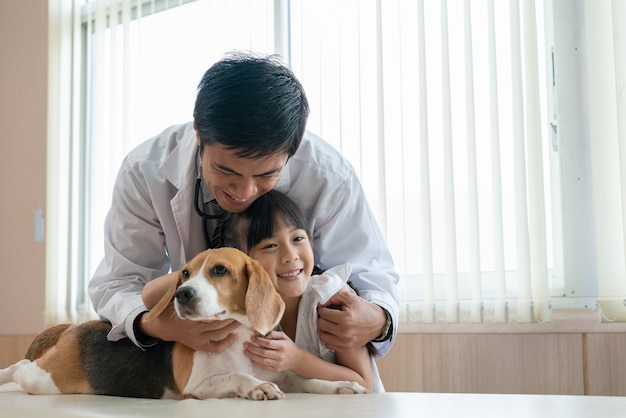 Lekarz weterynarii z małą dziewczynką przytulić słodkiego psa leżącego na stole po badaniu weterynarza w szpitalu