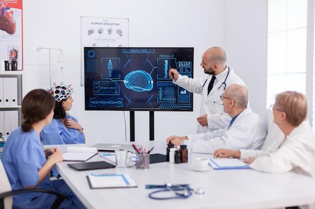 Lekarz wskazujący radiografię medyczną współpracownikom szpitala analizującym prezentację choroby mózgu przy użyciu zaawansowanych technologii w sali konferencyjnej
