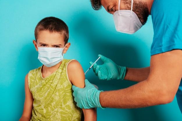 Lekarz wstrzykuje dziecku szczepionkę przeciwko krukowiczemu koronawirusowi