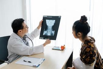 Lekarz wyjaśnia wyniki badania rentgenowskiego mózgu kobiecie w jego biurze w Ho