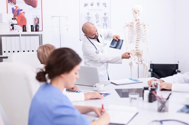 Lekarz wyjaśnia radiografii przed swoim personelem medycznym w sali konferencyjnej szpitala. ekspert kliniczny terapeuta rozmawiający z kolegami o chorobie, specjalista od medycyny
