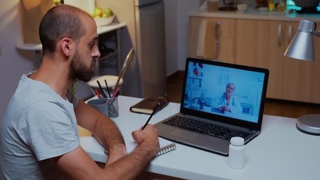 Lekarz wyjaśniający diagnozę podczas wideokonferencji i pisanie pacjenta na notebooku. lekarz udzielający konsultacji choremu pacjentowi z gabinetu szpitala podczas wirtualnego badania w godzinach nadliczbowych.