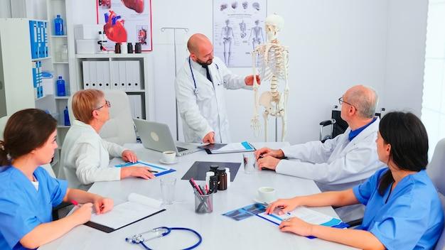 Lekarz wyjaśniający radiografię przed personelem medycznym w sali konferencyjnej szpitala przy użyciu modelu ludzkiego szkieletu. ekspert kliniczny terapeuta rozmawiający z kolegami o chorobie, specjalista od medycyny