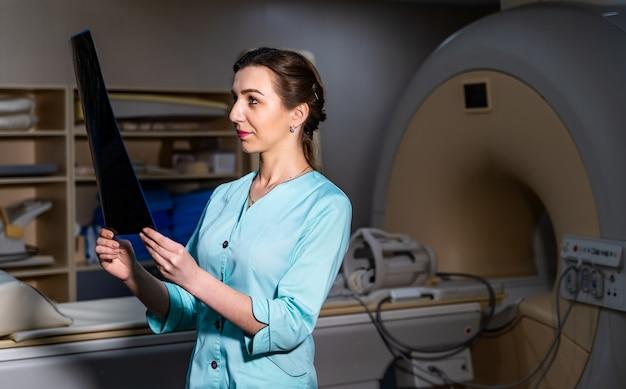 Lekarz wyjaśniający zdjęcie rentgenowskie w pobliżu maszyny do rezonansu magnetycznego.