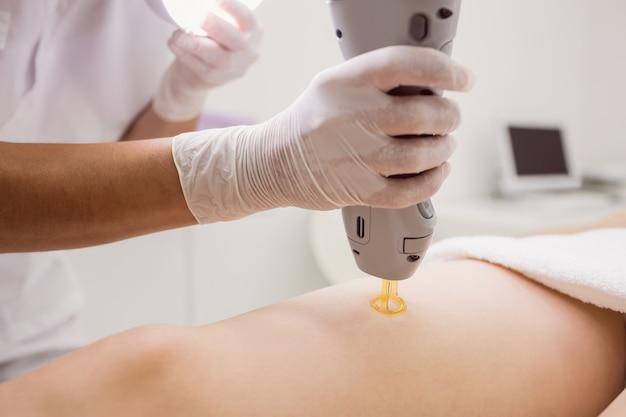 Lekarz wykonujący laserowe usuwanie włosów na kobiecej skórze pacjenta w klinice