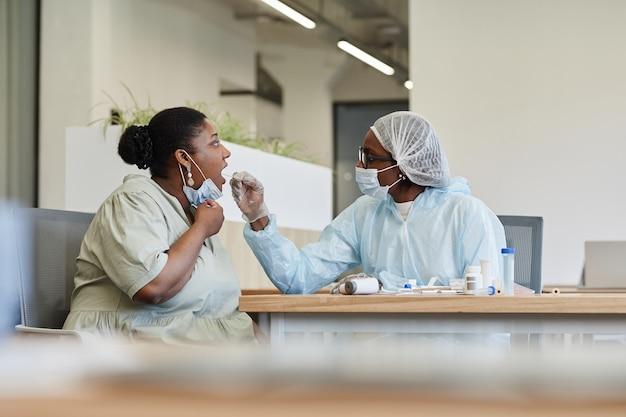 Lekarz wykonujący test na covid kobiecie z sondą do wymazu z gardła