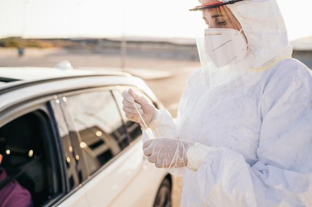 Lekarz wykonujący test pcr covid-19 na pacjencie przez szybę samochodu.