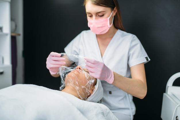 Lekarz wykonuje maseczkę na twarz, pozbywając się zmarszczek