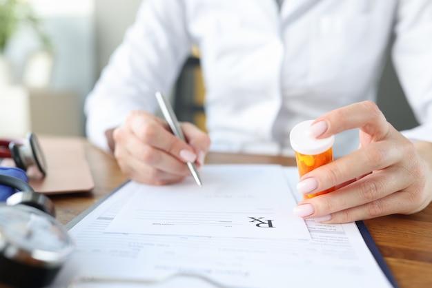 Lekarz wypisuje receptę i trzyma w rękach słoiczek z pigułkami. otrzymanie recepty na