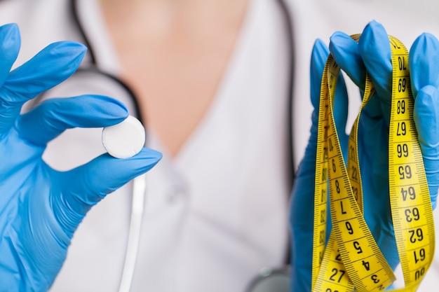 Lekarz z bliska trzymając białe tabletki na odchudzanie.