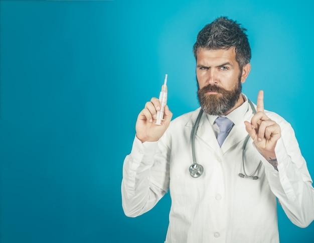 Lekarz z brodą i pewny siebie wyraz twarzy trzyma koncepcję gestu medycznego strzykawki medycznej
