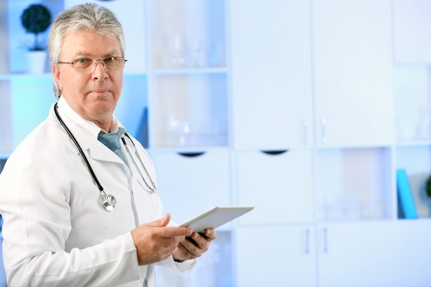 Lekarz z cyfrowym tabletem w swoim miejscu pracy