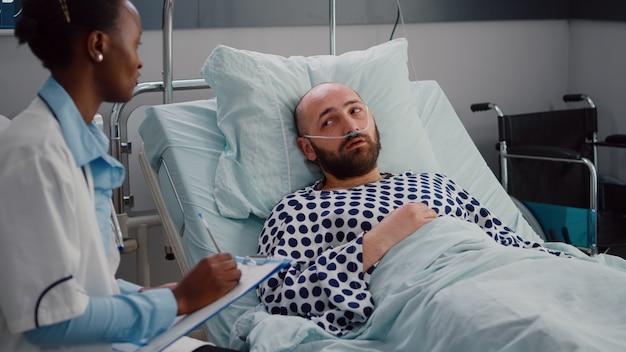 Lekarz Z Czarną Skórą Monitoruje Chorego Człowieka Piszącego Ekspertyzę Medyczną W Schowku Premium Zdjęcia