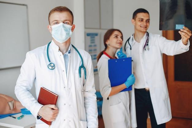 Lekarz z folderem w dłoniach patrzy w kamerę