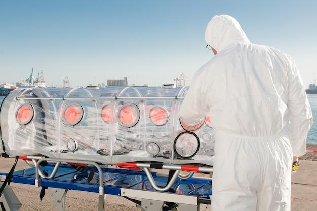 Lekarz z łóżkiem pogotowia izolowanym dla wirusa lub alarmu jądrowego