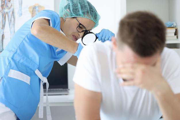 Lekarz z lupą bada odbytnicę pacjenta