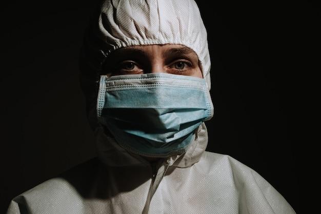 Lekarz z maską i osłoną twarzy na czarnym tle