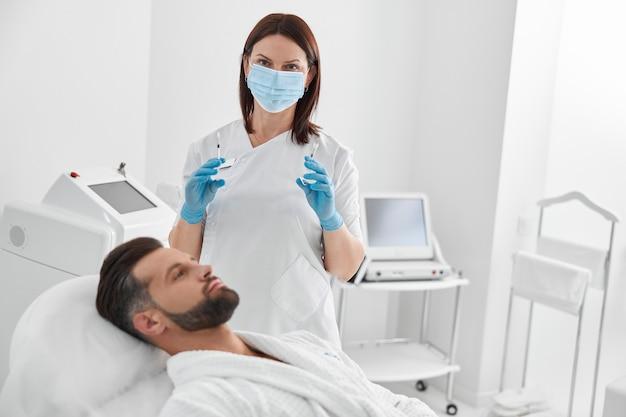 Lekarz z maską i wypełniaczami do liftingu skóry w pobliżu dojrzałego mężczyzny w klinice kosmetologicznej