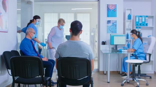 Lekarz z maską na covid 19 zapraszając pacjenta w sali egzaminacyjnej. pielęgniarka pomaga nieważny starszy kobieta z chodzeniem w poczekalni szpitala. system opieki zdrowotnej podczas globalnej pandemii