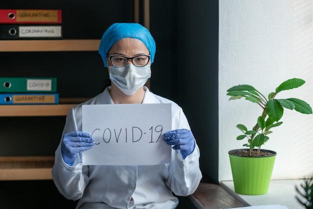 Lekarz z napisem covid-19 w rękach.