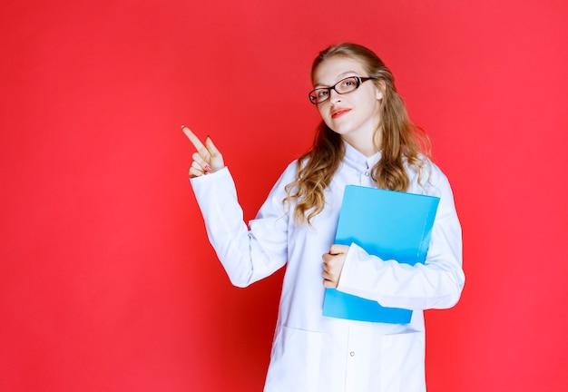 Lekarz z niebieską teczką wskazującą gdzieś lub kogoś.