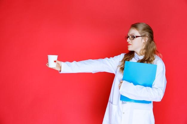 Lekarz z niebieskim folderem trzymając kubek wody.