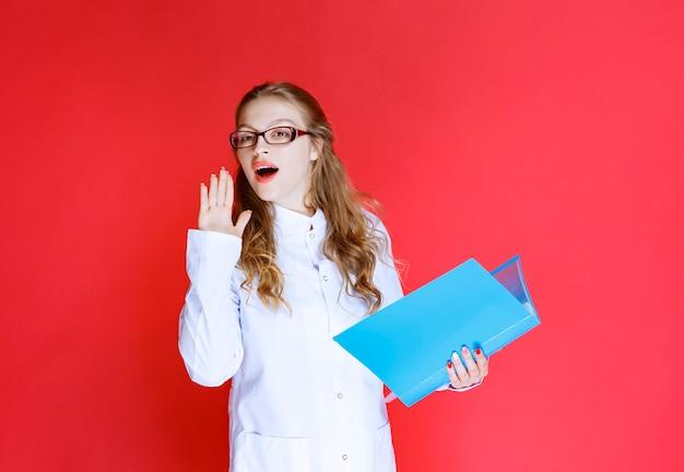 Lekarz z niebieskim folderem witającym jej pacjenta.