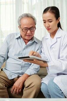 Lekarz z pacjentem za pomocą komputera typu tablet