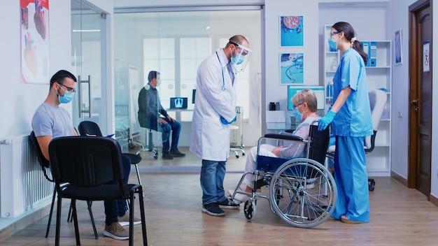 Lekarz z przyłbicą przeciw koronawirusowi zaprasza pacjenta do sali egzaminacyjnej z poczekalni, rozmawia z niepełnosprawną starszą kobietą na wózku inwalidzkim popychaną przez pielęgniarkę z maską na twarz.