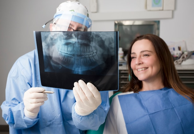 Lekarz z rentgenem jamy ustnej i sprzętem ochrony osobistej uczy pacjentki prześwietlenia jamy ustnej