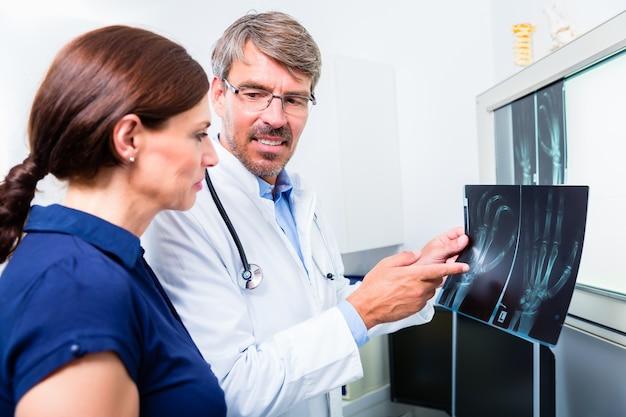 Lekarz z rtg ręki pacjenta w jego gabinecie, badanie obrazu
