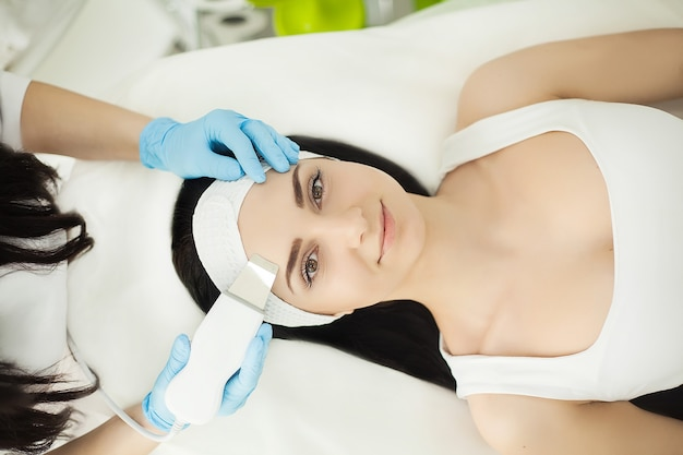 Lekarz z scraberem ultradźwiękowym. wykonanie zabiegu ultradźwiękowego czyszczenia twarzy. model, profil. klinika kosmetologiczna. cierpliwy. służba zdrowia, przychodnia, kosmetologia.