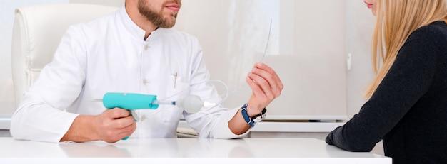 Lekarz z urządzeniem do usuwania żylaków wyjaśniający procedurę pacjentce. flebolog mężczyzna chirurg pracuje w nowoczesnej klinice. narzędzia medyczne w szpitalu. leczenie żylaków.