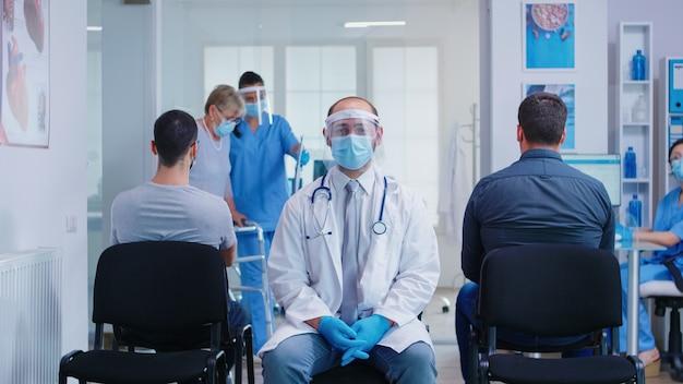 Lekarz z wizjerem przeciwko koronawirusowi w poczekalni, patrząc na kamerę intro. pielęgniarka z maską pomoc niepełnosprawna kobieta z chodzeniem w korytarzu szpitala.